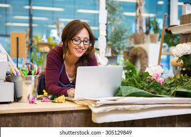 Happy mid adult female florist using laptop at counter in flower shop