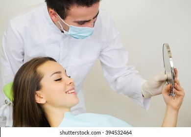 Happy mid adult female patient with doctor looking at mirror in clinic.Dentist