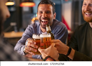 Happy mid adult friends clinking with beer mugs in pub. Three cheerful guys drinking draft beer, celebrating meeting and smiling. Laughing young men enjoying cold pint of beer during night at bar.  - Shutterstock ID 1721912764