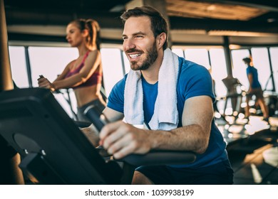 Happy mid adult man having fun in the gym. Bicycle for better cardio workout.