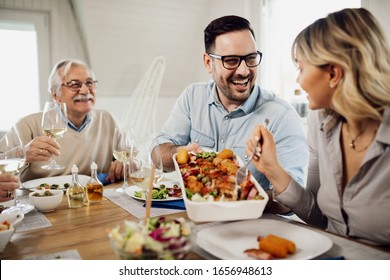 Happy mid adult man talking to his wife while passing her food during family lunch at home.