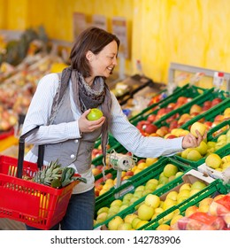 Happy mid adult woman with shopping basket choosing apples in grocery store