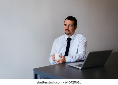 Happy mid age man in suit drinking coffee