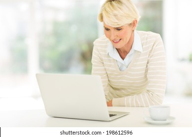 happy mid age woman using laptop computer at home