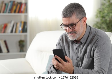 Happy mid aged man using a smart phone at home