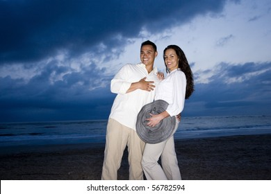 Happy mid-adult Hispanic couple smiling on beach at dawn