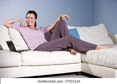 Happy mid-adult woman sitting on couch smiling with laptop
