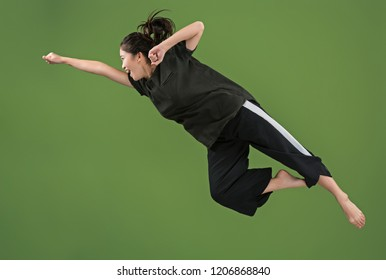 I am happy. Mid-air shot of pretty smiling young woman jumping and gesturing against green studio background. Runnin girl in motion or movement. Human emotions and facial expressions concept