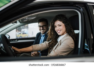 Happy middle age couple enjoying while choosing and buying new car at showroom.