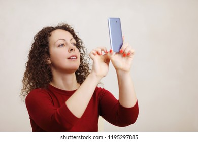 Happy middle age curly pretty woman in red makes selfie by smartphone in white room
