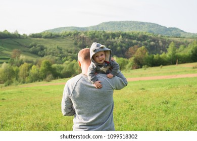 Happy middle age man holding his little baby. Father carries a child on his shoulder