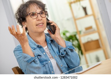 an happy middle age woman with glasses using and talking phone