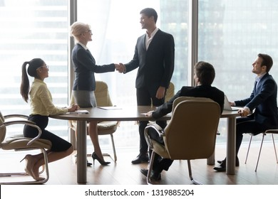 Happy middle aged boss leader handshaking african businessman welcoming greeting new partner at team meeting in boardroom, diverse executives shake hand as promotion respect and rewarding concept