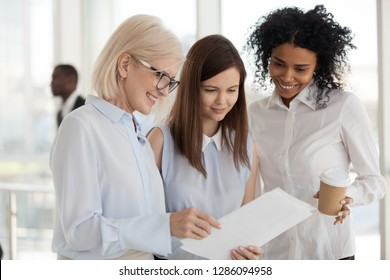 Happy middle aged business lady female director showing to multiracial worker women documents about cash monetary bonus for all employees for a job well done or project completion, good news concept