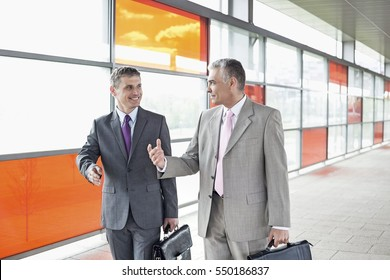 Happy middle aged businessmen talking while walking in railroad station