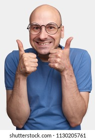 Happy middle aged caucasian bald man wearing eyeglasses and t-shirt making thumb up sign and smiling cheerfully