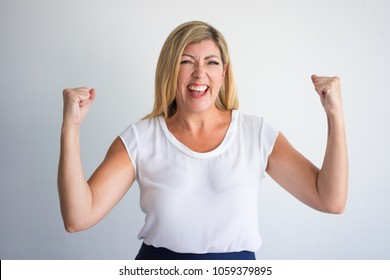 Happy middle aged Caucasian woman raising fists in winning gesture and celebrating success. Mature woman gaining prize or hitting jackpot. Win and success concept