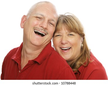 Happy middle aged couple laughing together.  Isolated on white.