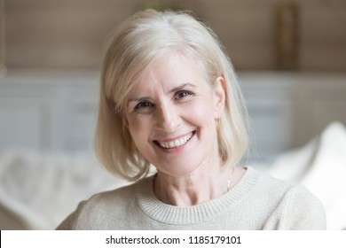 Happy middle aged elderly grey haired woman looking at camera posing at home indoors, positive satisfied single mature senior retired lady with wide toothy smile headshot portrait, natural old beauty