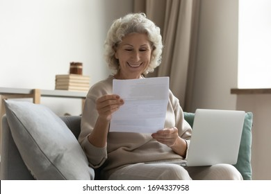 Happy middle aged elderly woman sitting on couch, holding computer on knees lap, reading paper document or mail letter from friend. Smiling mature old grandmother excited by good news notification.