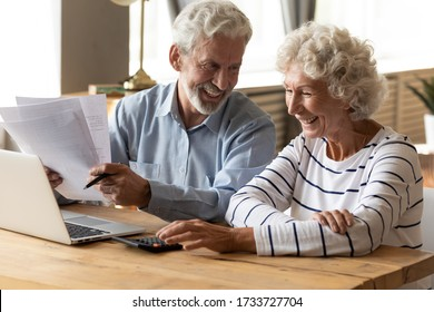 Happy middle aged family spouses sitting at table with computer and paper bills, calculating domestic incomes together at home. Smiling friendly mature senior married couple managing monthly budget.
