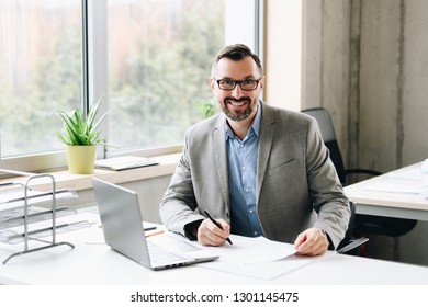 Happy middle aged handsome businessman in shirt working on laptop computer in office. Man working in office
