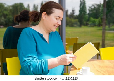 Happy middle aged lady enjoying novel and espresso in street cafe. Smiling Caucasian woman reading book or menu in coffee shop. Leisure or coffee break concept
