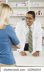 Happy middle aged male pharmacist explaining the prescription to customer at workplace