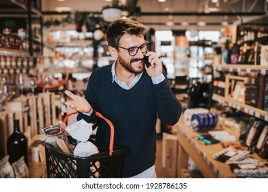 Happy middle aged man buying healthy food and drink in a modern supermarket and talking on phone.
