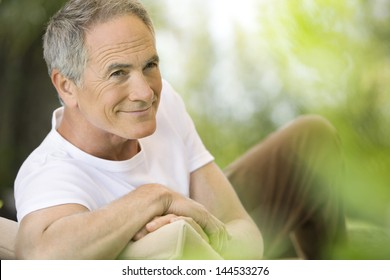 Happy middle aged man reclining on deck chair in garden