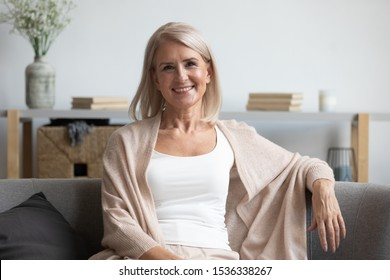Happy middle aged mature woman looking at camera sitting alone on sofa at home, smiling attractive senior adult old retired lady relaxing sitting on couch in apartment living room posing for portrait