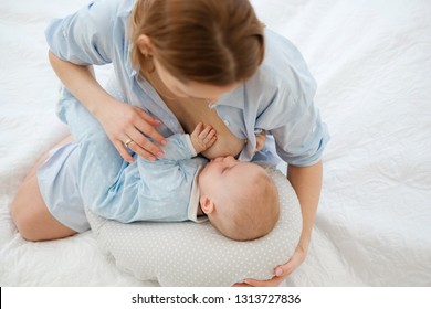 Happy middle aged mother breast feeding her baby