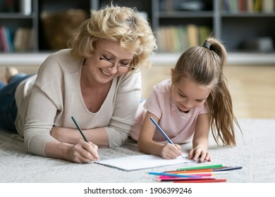 Happy middle aged older woman in eyeglasses lying on floor carpet with smiling adorable preschool little kid girl, enjoying drawing together in paper album, daycare activity, babysitting concept.
