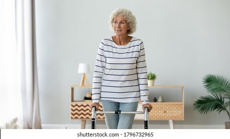 Happy middle aged senior hoary retired woman using walking frame, enjoying rehabilitation procedures indoors. Smiling older disabled grandmother making steps with walker, handicapped people lifestyle.