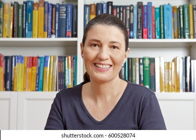 Happy middle aged woman with blue t-shirt in front of lots of books, having an live video chat with her family or onlne dating