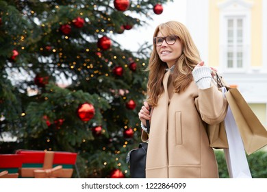 Happy middle aged woman carrying shopping bags while walking in shopping centre outdoor and shopping gifts for Christmas.