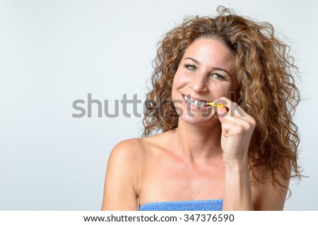 happy middle aged woman cleaning her teeth with an interdental brush, while smiling in to the camera