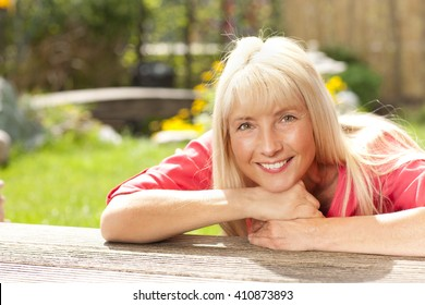 Happy middle aged woman leaning over wooden Terrace in the garden