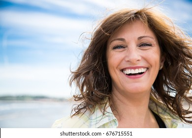 Happy middle aged woman with messy hair laughing on the beach
