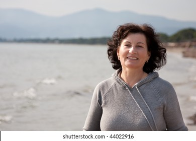 Happy middle aged woman portrait enjoying a day at the beach