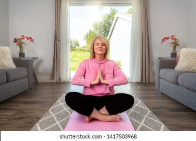 Happy middle aged woman practicing healthy living yoga, meditation, inner peace, relaxation, alone in home