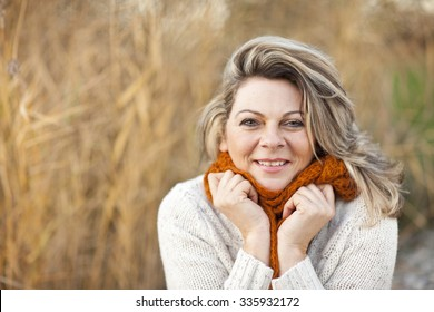 Happy middle aged woman with pullover and scarf outdoor