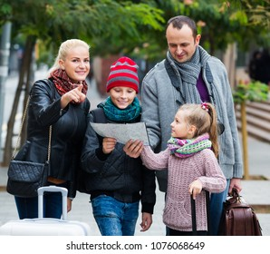 Happy middle class family of four checking a direction in the map
