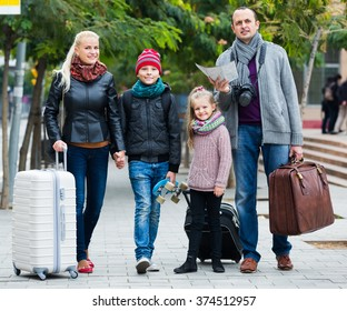 Happy middle class family of four checking a direction in the city map