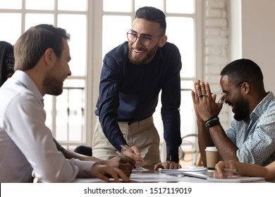 Happy middle eastern ethnicity young manager having fun with mixed race colleagues during brainstorming meeting at office. Positive diverse business team laughing, joking at project discussion.