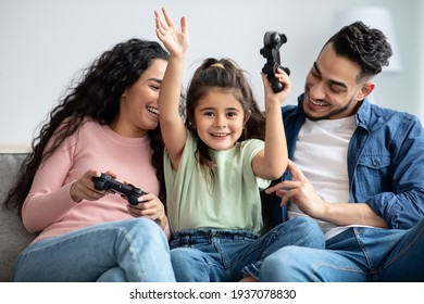 Happy middle eastern family of three playing video games together at home