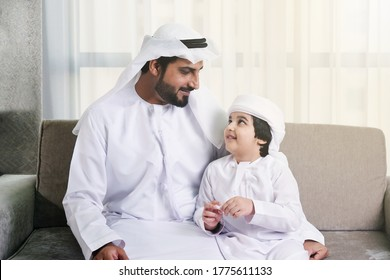 Happy Middle Eastern father and son on Kandura. Arab father and son together at home keeping safe from COVID pandemic virus outbreak doing self quarantine. Arabic national on traditional dishdash