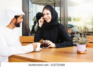 Happy middle eastern man talking to a woman over cup of coffee