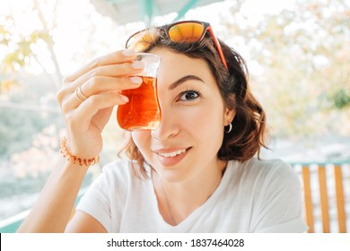 Happy middle Eastern woman drinks traditional Turkish tea on the veranda or terrace of an outdoor restaurant