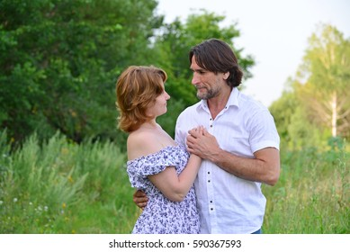 Happy middle-aged couple on a nature in summer